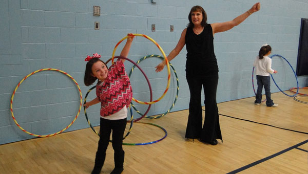 Hoop for Fitness instructor Ann Kirkland helps Alyssa Brown morph into a butterfly. (contributed)