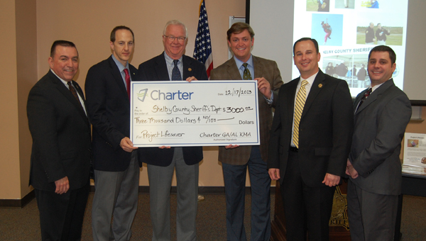 Charter Communications employees present a $3,000 check to the Shelby County Sheriff's Office that will be used for Project Lifesaver. (Reporter Photo/Stephanie Brumfield)