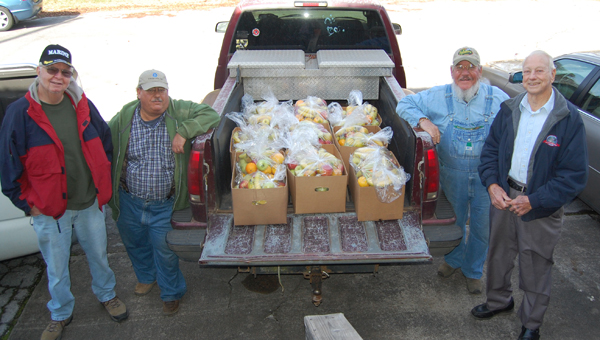Gene Howell, Jon King, Ben King and Gene Duffey load a truck with bags of fruit to distribute to the elderly and widows around Columbiana Dec. 19. (Reporter Photo/Stephanie Brumfield)