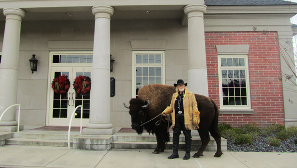 Cody the Buffalo with his owner, Mike Fogel, stand in front of Bryant Bank in Columbiana Dec. 13. (Reporter Photo/Stephanie Brumfield)