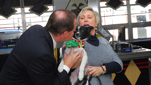 State Sen. Cam Ward, left, kisses Alabaster's canine mascot, Warrior, as Alabaster City Schools employee Wendy McNish, right, looks on. (Reporter Photo/Neal Wagner)