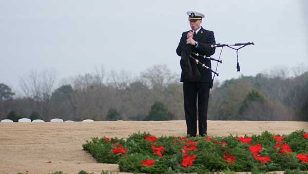 A service member plays the bag pipes during a Wreaths Across America wreath-laying ceremony at Alabama National Cemetery.