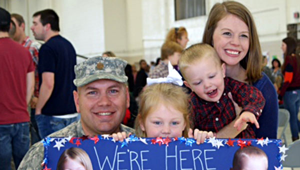 """We're Here to get Our Daddy"" read the sign Laura Griffin and her children Abby and Carter made for husband and father Mac Griffin, who returned after 11 months from deployment in Kuwait. (Contributed)"