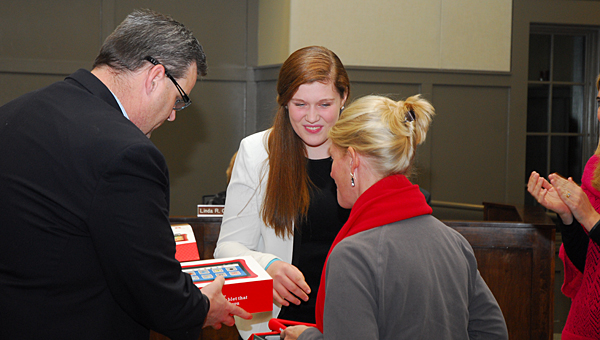 THS junior Katelyn Molan, center, and her father, Bobby, donate two tablets to the THS special education department during a Jan. 15 Alabaster School Board meeting. (Reporter Photo/Neal Wagner)