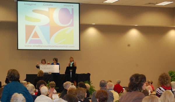 Vignette Club president hands over check for $1,000 to Shelby County Arts Council executive director Terri Sullivan.