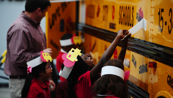 Students from the Alabama Institute for Deaf and Blind place decals on a school bus during the Love the Bus event on Feb. 4 in Pelham. (Reporter Photo/Jon Goering)