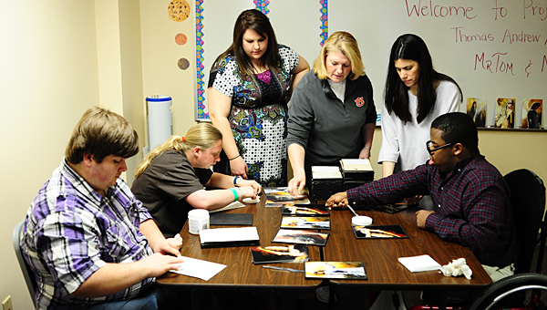 Students with Project SEARCH work to create pieces of art during a Feb. 21 event at the program's office in Alabaster. (Reporter Photo/Jon Goering)