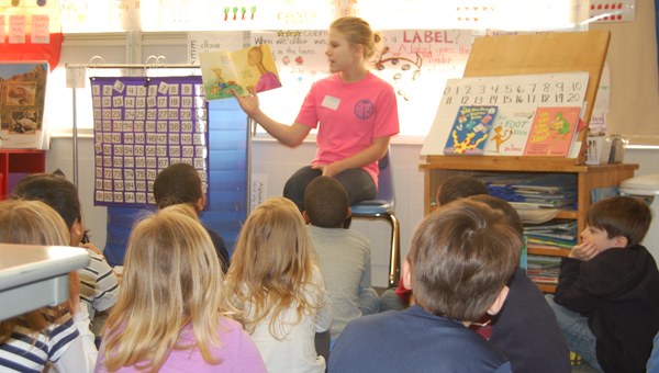 Middle school student reads to elementary school children as part of the Riverchase Middle School's literary program. (Contributed)