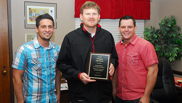 Cultivate Church pastors Brandon Matthews, left, and Brandon Doss, right, present a plaque to Thompson High School Principal Dr. Daniel Steele, center, on March 21. (Reporter Photo/Neal Wagner)