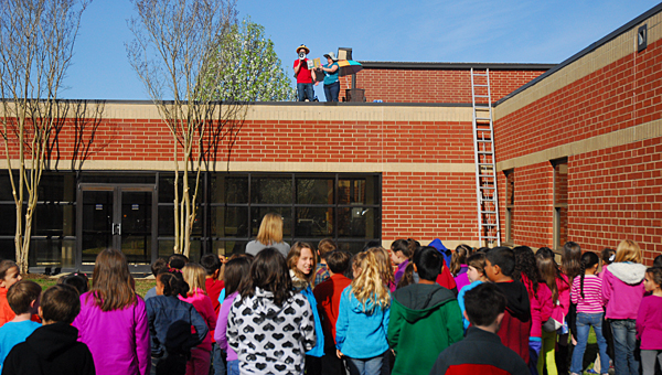 Creek View Elementary School teachers read to students from the school's roof on March 21. (Reporter Photo/Neal Wagner)
