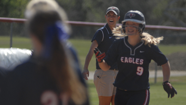 Oak Mountain head coach Kellie Eubanks looks on while Cassady Greenwood (No. 9) celebrates after hitting her first career hoe run in a 4-3 win over Hoover April 11. (Reporter Photo/Drew Granthum)