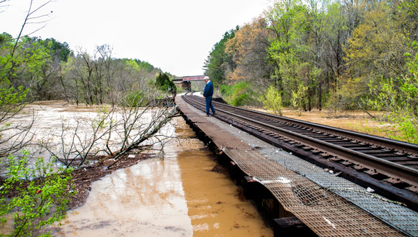 At noon on April 7, Ken Penhale views floodwaters rising to the underside of the railroad trestle just west of Old Town Helena. (Contributed)