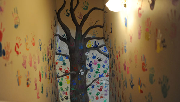 Child abuse victims and sometimes their family members leave a handprint on a mural of a tree downstairs when they complete their time at Owens House – a sign to future visitors that others have walked in their shoes. (contributed)