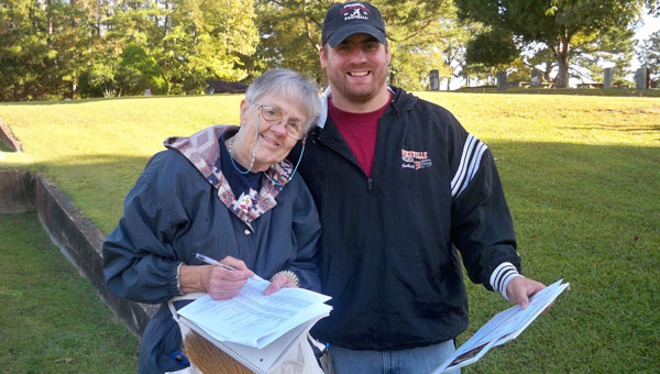 Latter-Day Saints volunteers Claudiann Tilton and Sean McKinley identify graves at the Columbiana City Cemetery. Tilton received the RSVP Spirit Award for her thousands of hours volunteering on this project and others. (Contributed)