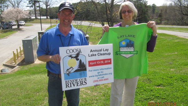 Mike Clelland, Alabama Power Stewardship Coordinator, and Judy Jones, Lay Lake Home Owners and Boat Owners clean up chair for the last 15 years, holding clean up display signs and new 15th anniversary T shirts. (Contributed)