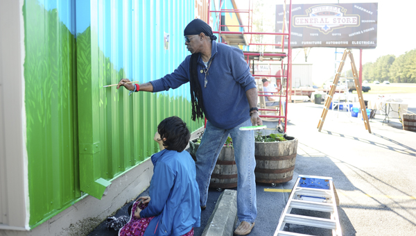 Artist John Sandridge assists Chelsea High School student Rebecca Harrison as she works on the Chelsea General Store mural April 9. (Reporter Photo|Jon Goering)