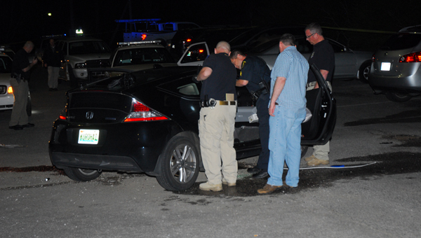 Helena, Pelham and Alabama Bureau of Investigation agents examine a suspect's vehicle after a shooting in the parking lot of Helena's Papa Saia's restaurant. (Reporter Photo/Neal Wagner)