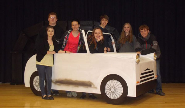 Members of the cast for Vincent Middle High's production of Grease pose in front of a prop (contributed)