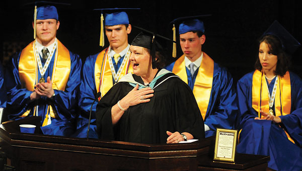 With the valedictorians seated behind her, Hope Christian School Administrator Connie Atchison reads a letter from a parent during the May 19 graduation ceremony. (Reporter Photo/Jon Goering)