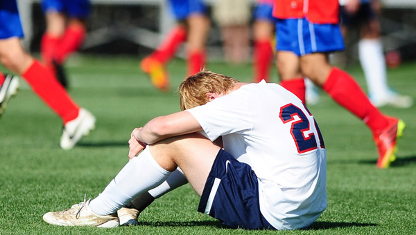A member of Oak Mountain's boys soccer team sits in thought after falling the AHSAA Class 6A soccer state finals. (Reporter Photo/Jon Goering)