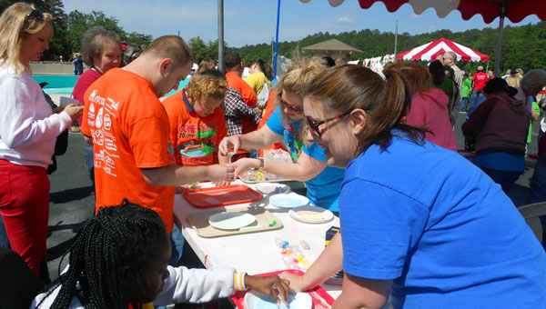 Volunteers at an activity station helped students create sand neck- laces at the annual Gone Fishin' Not Just Wishin' event on May 16. (contributed)