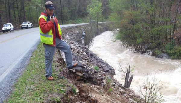 "Clay Adderholt, Shelby County highway operations supervisor, inspects recent flooding damage to Shelby County 280 in ""The Narrows."" (Contributed)"