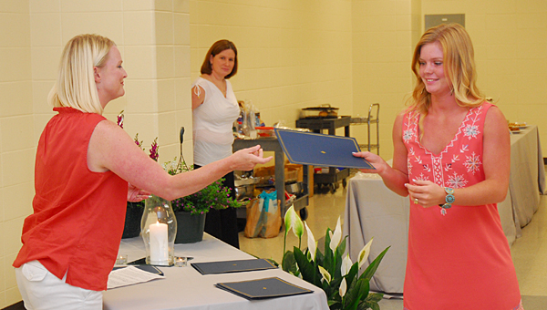 THS English teacher Kim Windham, right, presents a $1,000 scholarship to THS senior Sara Beth Holdbrooks during a reception on May 13. (Reporter Photo/Neal Wagner)