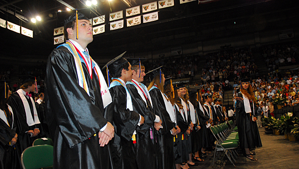 Thompson High School graduate and valedictorian Christopher Lewis Jr., left, prepares to take his seat during the school's May 20 graduation ceremony at Bartow Arena in Birmingham. (Reporter Photo/Neal Wagner)