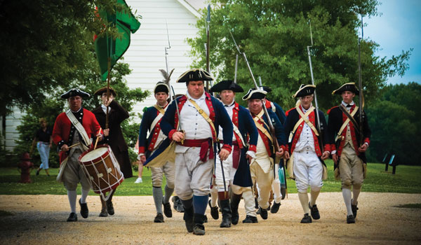 Historical interpreters march through the American Village during a past Memorial Day. (Contributed)