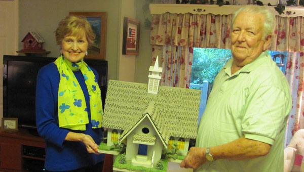Barbara and Emmett Waldrop display one of their handmade birdhouses modeled after a church. (Contributed)
