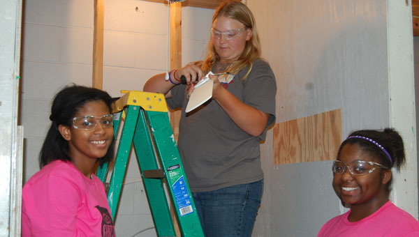 Tyelyn Maddox, Alison Walls and Zoe Dukes work together to install a ceiling fan at the Girls Can Construction Camp in Columbiana. (contributed)