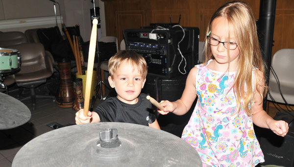 Brother and sister Maycie and Zane Lewis take time to try out the drums and cymbals after the first summer reading library program. (Contributed)