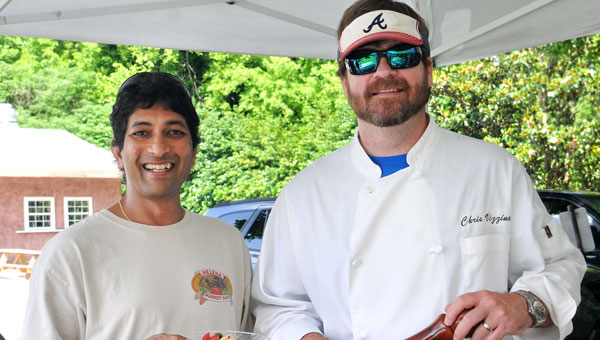 Zulfi Merchant, (left) the new volunteer procurer for chefs and special demos at Helena Market Days samples a seasonal summer entrée prepared by guest Chef Chris Vizzina. (Contributed)