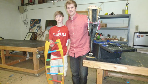 Parker Owen (right) with brother John Thomas Owen in their father Scott Owen's shop. John Thomas is holding a DNA model built by his brother. Parker is holding his Cycle-Leg invention. (Contributed)