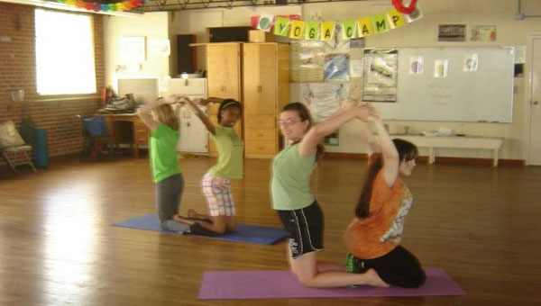 Teens at last summer's Teen Yoga Camp in Montevallo practice a partner pose. (Contributed)