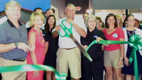 Helena Health Club owner Terry Brasseale cut the ribbon officially opening the gym during a June 19 grand opening celebration. (Reporter Photo / Molly Davidson)