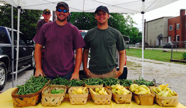 Trey Colley and Zack Smith in front of their remaining produce at the first farmer's market of the season in Montevallo. (Ginny Cooper/Reporter photo)
