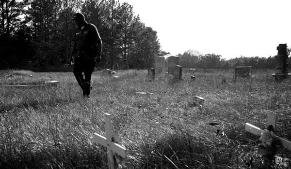 Albert Datcher walks through the family cemetery, which he worked to preserve. (Reporter Photo/Jon Goering)