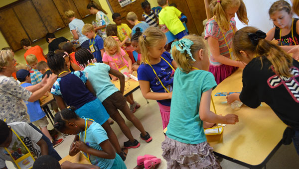 Children work to level a ruler with coins and a bottle to illustrate balance during a science session at Montevallo First United Methodist Church's VBS. (contributed)