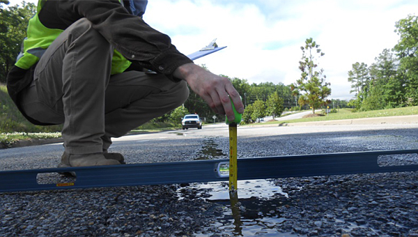 Crews measure dips and potholes during a previous inspection of Alabaster Boulevard. The road soon will see repairs. (File)