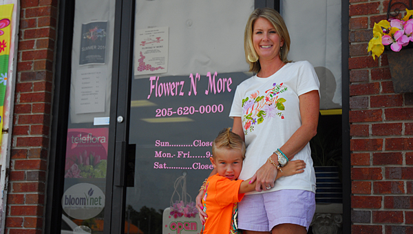 Melanie Shores and her son, Tucker, prepare for Flowerz 'N More's grand opening ceremony on July 17. (Reporter Photo/Neal Wagner)