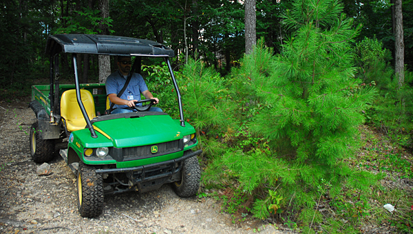 ACS Operations Coordinator Dr. Jeff Atkins drives an all-terrain vehicle on the future site of the city's new high school and athletic complex between Thompson Road and Kent Dairy Road. The city's School Board voted to move forward with bonds for the project on Aug. 20. (File)