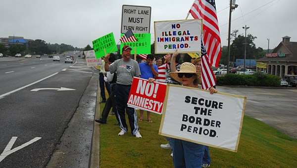 "A group protests illegal immigration during a rally on U.S. 280 on July 19. The event was part of the ""Make Them Listen"" campaign organized across the nation from July 18-19. (Reporter Photo/Neal Wagner)"
