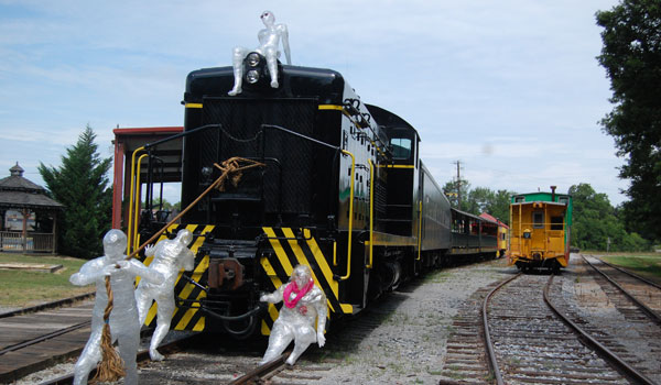 University of Montevallo students created this installation featuring four figures created from clear packing tape at the Heart of Dixie Railroad Museum on July 15. (Reporter Photo/Ginny Cooper McCarley)