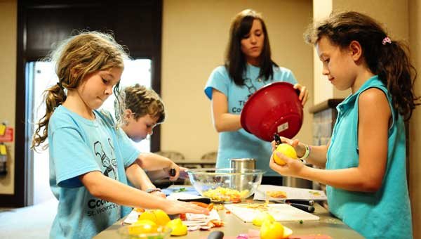 Campers prepare food in St. Vincent's One Nineteen  Thyme to Cook for Kids camp. (Reporter Photo/Jon Goering.)