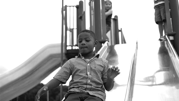 Joshua Williams slides down the slide at Meadow View Elementary while his classmates, Macy Holt and Dylan Bell, look on, during the first day of school. (Reporter Photo/Jon Goering)
