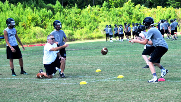 Coach Watt Parker, left, works with players on the brand new Helena Husky football team in late summer drills on the field at Helena Middle School. (Contributed)