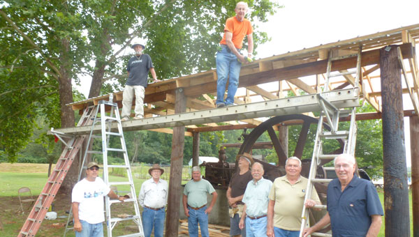 Historic Shelby Association members roof a new shed covering Hardie-Tynes cordless steam engine at Shelby Iron Park on Highway 42 in Shelby. (Contributed)