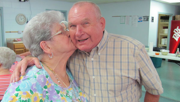 Former mill employee Betty Ray greets Lloyd Davenport with a kiss. (Contributed)