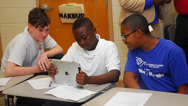 Thompson Middle School students, from left, Matthew Eubanks, Durrell Russel and Julius Bray use an iPad to complete lessons in Todd Davis' geography class on Aug. 21. (Reporter Photo/Neal Wagner)